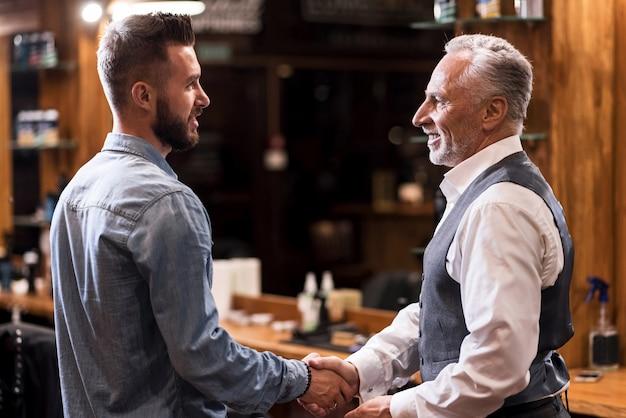 Dwa pokolenia. solidny starszy mężczyzna stojący i ściskający dłonie z przystojnym młodym fryzjerem w zakładzie fryzjerskim.