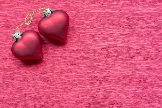 Dwa połączone serca na czerwonym tle papieru