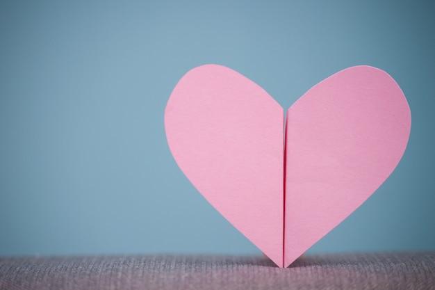 Dwa połówki papieru serce na błękitnym tle.
