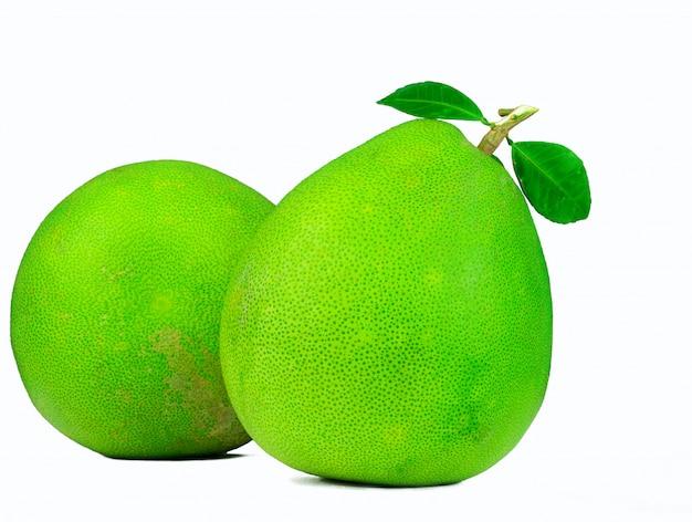 Dwa pomelo z liśćmi odizolowywającymi. owoc tropikalny. owoc cytrusowy. zielone owoce.