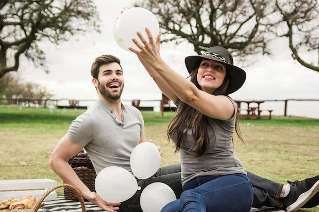 Dwa potomstwa dobierają się bawić się z białymi balonami w parku