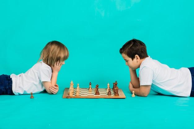 Dwa poważne chłopiec gra w szachy w studio, niebieskie tło