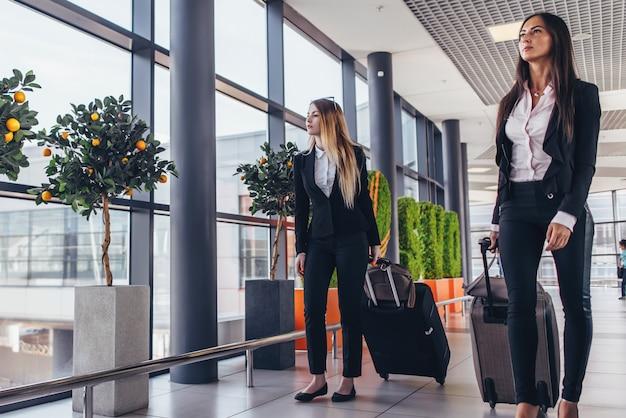 Dwa poważnego młodego żeńskiego kolegi chodzi przez lotniskowego przejścia niesie walizki