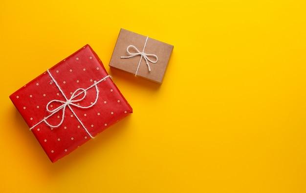 Dwa prezenty zawinięte w papier rzemiosła na żółtym tle.