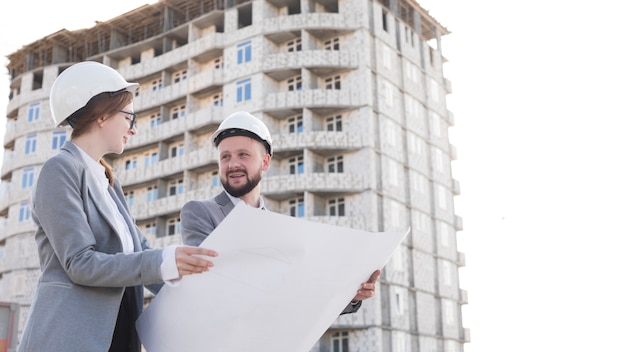Dwa profesjonalny uśmiechnięty inżynierii gospodarstwa plan i patrząc na siebie