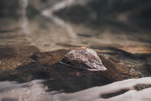 Dwa proste złote pierścionki zaręczynowe stoją na szarym kamieniu pośrodku przezroczystej, krystalicznej wody