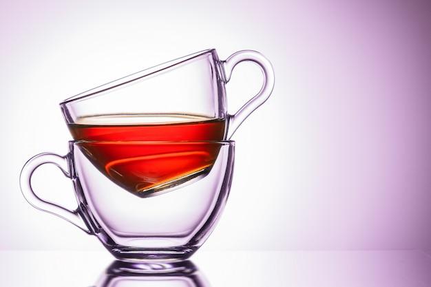 Dwa przezroczyste kubki herbaty. lokalizacja po lewej, zbliżenie. różowy odcień
