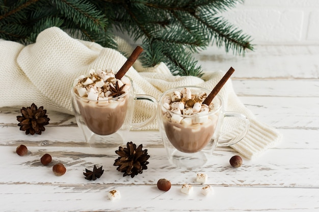 Dwa przezroczyste kubki z podwójnym dnem z gorącą czekoladą i pianką marshmallow na białym drewnianym tle. koncepcja świąt noworocznych.