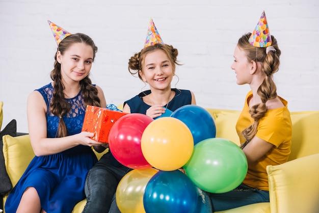 Dwa przyjaciela daje teraźniejszość urodzinowy dziewczyny obsiadanie na żółtej kanapie