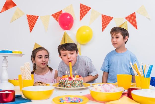Dwa przyjaciela patrzeje chłopiec dmucha świeczki na urodzinowym torcie