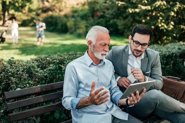 Dwa przystojnego biznesowego mężczyzna patrzeje pastylkę podczas gdy siedzący na ławce.