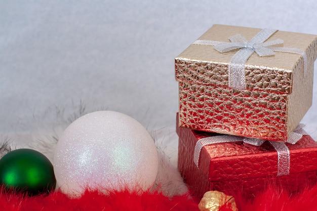 Dwa pudełka na prezenty i dwie bombki na białe i czerwone futro na białym tle. czerwone i złote pudełka stoją jeden na drugim. zielona i biała piłka.