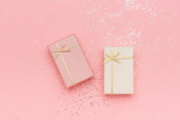 Dwa pudełka na prezenty pastelowych kolorów na różowym tle, widok z góry