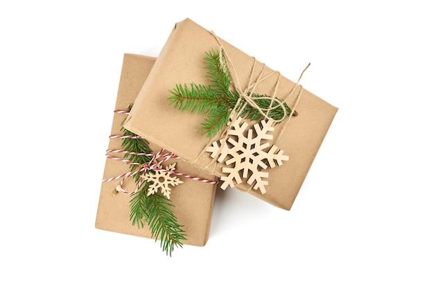 Dwa pudełka na prezenty świąteczne ozdobione gałązką jodły i drewnianymi płatkami śniegu