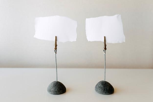 Dwa puste kawałki papieru do pisania notatek na stojaku.