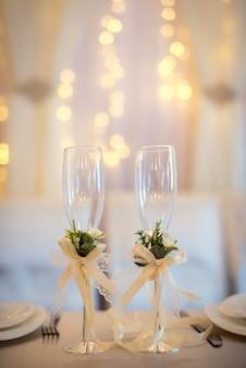 Dwa puste kieliszki do szampana weselnego z kremowymi kokardkami i kwiatowym wystrojem na stole.