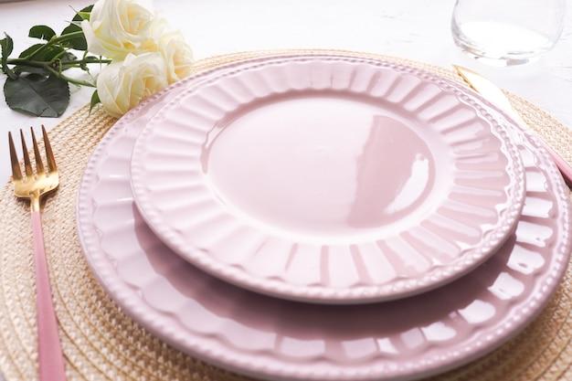 Dwa puste różowe talerze, róże w wazonie, łyżka i widelec na białym stole