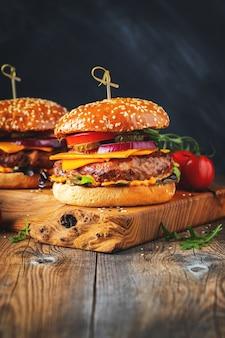 Dwa pyszne domowe burgery z wołowiny, sera i warzyw na starym drewnianym stole. tłuszcz niezdrowe jedzenie zbliżenie ..