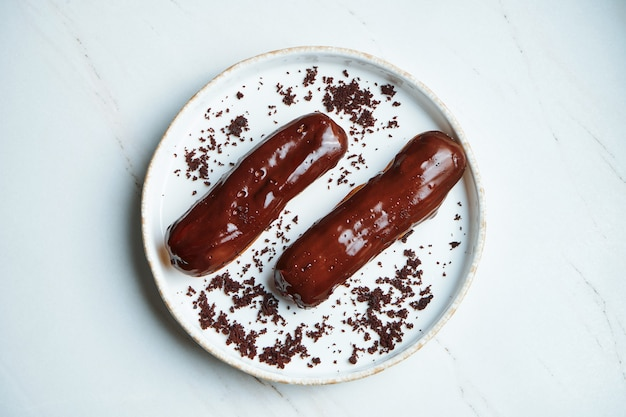 Dwa pyszne eklery z kremem i błyszczącym lukrem czekoladowym na białym talerzu ceramicznym na marmurowej powierzchni. apetyczny deser i ciastka. widok z góry, poziomy