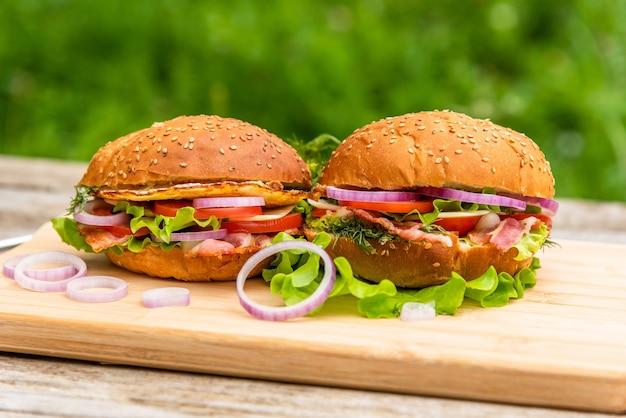 Dwa pyszne hamburgery z boczkiem, sałatą i posiekaną cebulą.