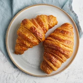 Dwa pyszne rogaliki na talerzu i gorący napój w kubku. rano francuskie śniadanie ze świeżymi wypiekami