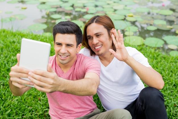 Dwa radośnego mężczyzna bierze selfie na pastylce w parku