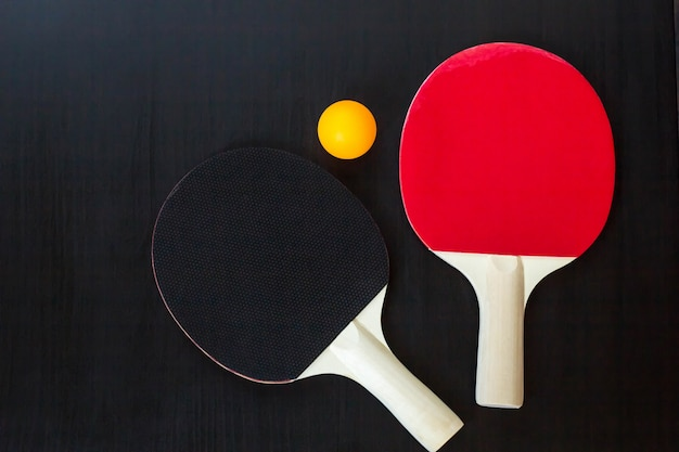 Dwa rakiety do tenisa stołowego lub ping ponga i piłkę na czarnym tle