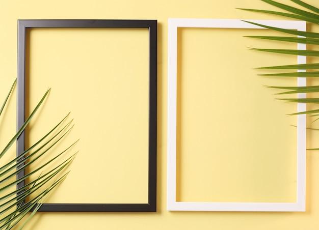 Dwa ramki na zdjęcia i liści palmowych na pastelowym żółtym tle