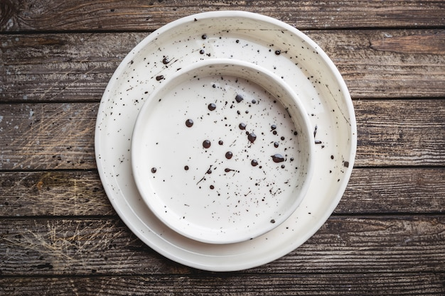 Dwa ręcznie robione puste białe talerze na drewnianym tle. widok z góry z miejscem na kopię