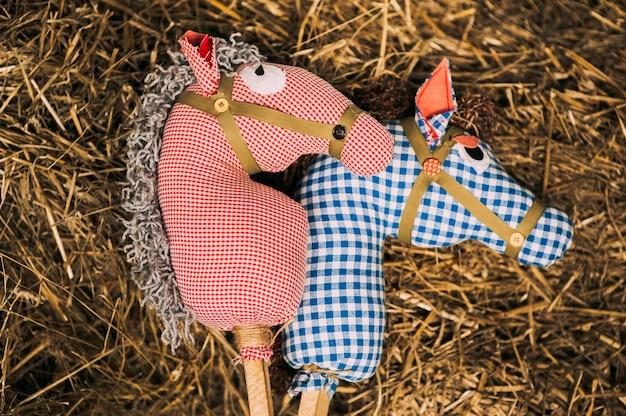 Dwa retro bawełniane zabawki koń na patyku leżącym na sianie. konie w czerwono-niebieską kratkę to zabawki do zabaw dla dzieci lub teatru lalek. tło rustykalne.