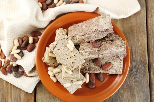 Dwa rodzaje chałwy słonecznikowej- z kakao i orzeszkami ziemnymi na talerzu, na drewnianym stole