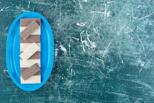 Dwa rodzaje chrupiących gofrów na niebieskim talerzu.
