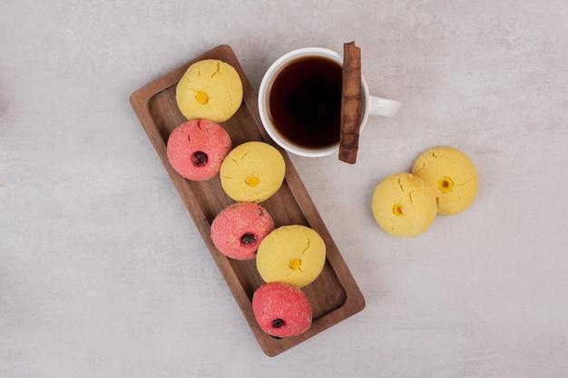 Dwa rodzaje ciasteczek i filiżankę herbaty na białym stole.