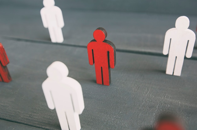 Dwa rodzaje drewnianych postaci na drewnianym stole: czerwone i białe