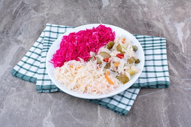Dwa rodzaje kiszonej kapusty i pikle na białym talerzu z obrusem.