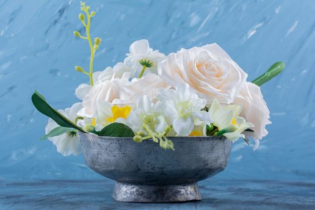 Dwa rodzaje kwiatów umieszczone w metalowej misce na niebiesko.