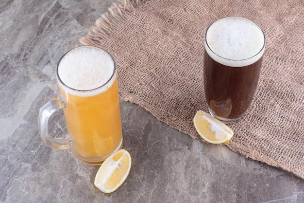 Dwa rodzaje piw na marmurowej powierzchni z cytrynami. zdjęcie wysokiej jakości