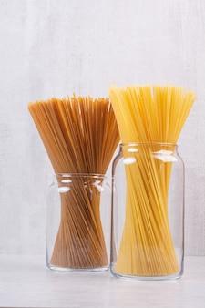 Dwa rodzaje spaghetti w szklanych słoikach