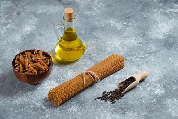 Dwa rodzaje surowego makaronu i szklana butelka oleju.