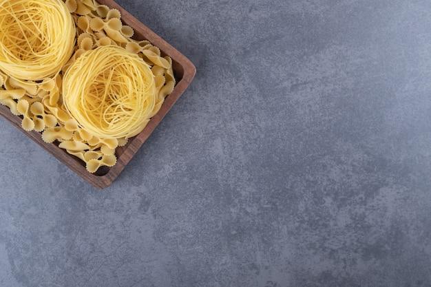 Dwa rodzaje surowego makaronu na desce.