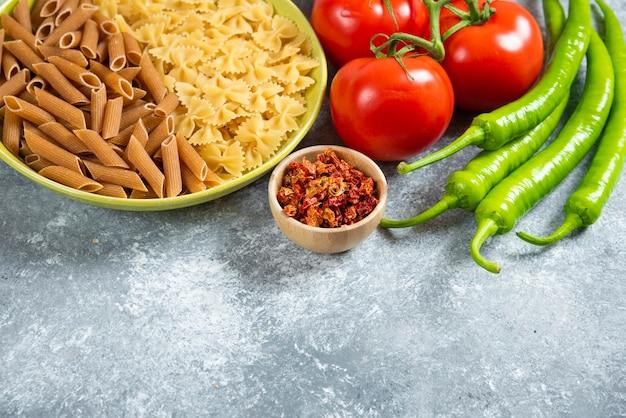 Dwa rodzaje surowego makaronu na zielonej tablicy ze świeżymi warzywami.
