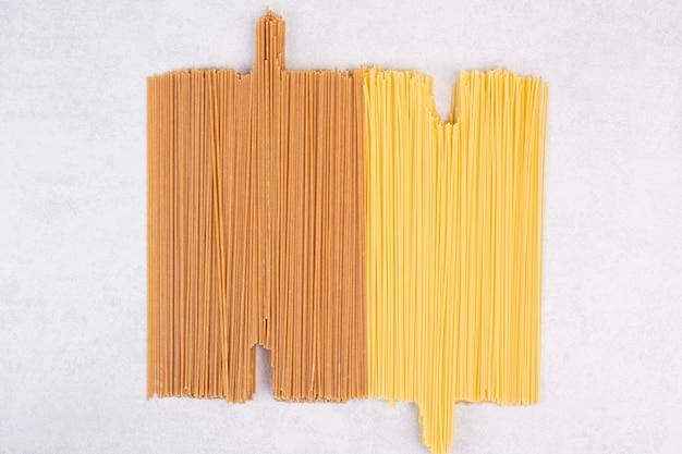 Dwa rodzaje surowego makaronu spaghetti na białej powierzchni