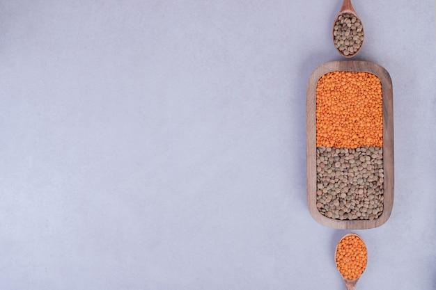 Dwa rodzaje surowej fasoli i soczewicy w drewnianym talerzu z łyżkami.