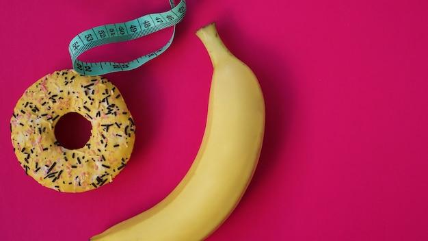 Dwa rodzaje żywności, zdrowe i niezdrowe, banan i pączek, dieta i otyłość, koncepcja zdrowia na różowym tle