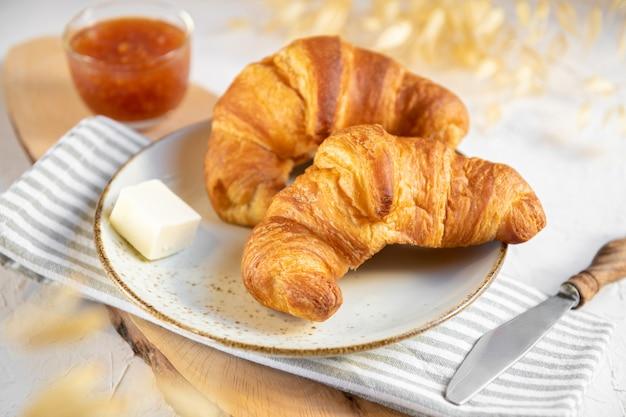 Dwa rogaliki na talerzu ceramicznym z masłem i konfiturą pomarańczową na drewnianej desce do krojenia. śniadanie kontynentalne, z bliska