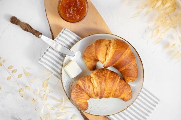 Dwa rogaliki na talerzu ceramicznym z masłem i konfiturą pomarańczową na drewnianej desce do krojenia. widok z góry.