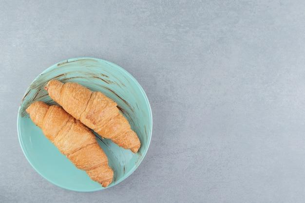 Dwa rogaliki na talerzu, na marmurowym tle. wysokiej jakości zdjęcie