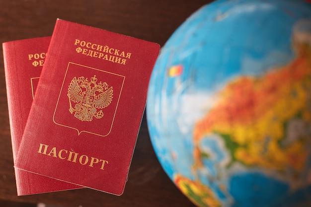 Dwa rosyjskie paszporty i globus. odpocznij, podróżuj