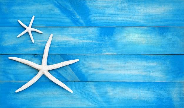 Dwa rozgwiazda na błękitny drewnianym. widok z góry