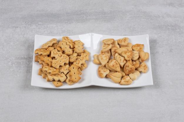 Dwa różne rodzaje krakersów na białym talerzu.